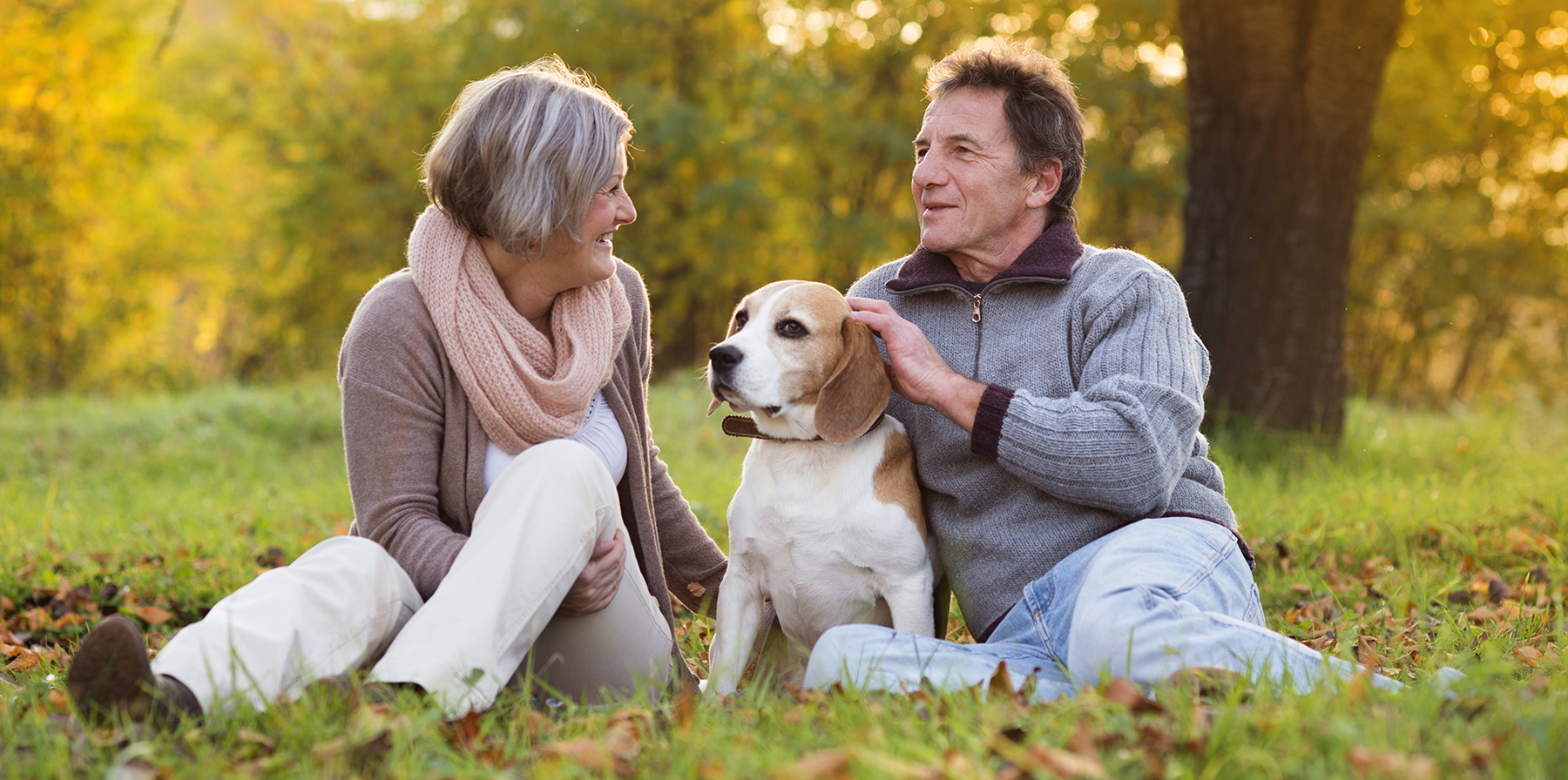 Couple seated in the grass with their pet beagle.